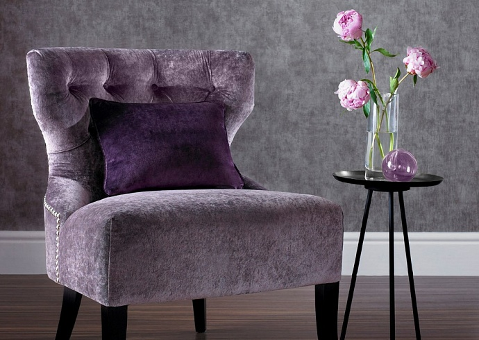 Purple upholstered chair and purple pillow with purple flowers on a table